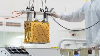 Technicians carefully lower the Mars Oxygen In-Situ Resource Utilization Experiment (MOXIE) instrument into the belly of the Perseverance rover.