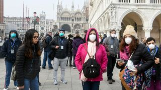 Tourists wearing protective masks visit Venice on Feb. 25, 2020, during the usual period of the Carnival festivities, which have been cancelled following the outbreak of COVID-19, caused by a novel coronavirus, in northern Italy.