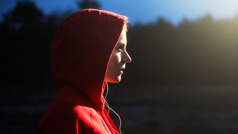 Young woman in hooded top listening to music. - stock photo