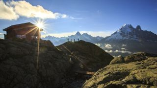 hut to hut hiking: hikers by a high mountain refuge in the French Alps