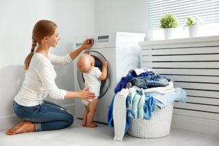 Mom putting laundry in washing machine.