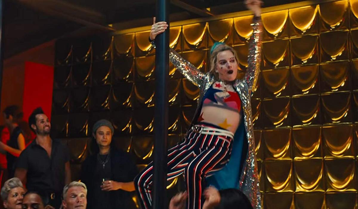 Margot Robbie as Harley swinging on a pole in Birds of Prey