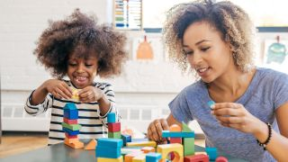 Mom and child playing with wooden blocks.