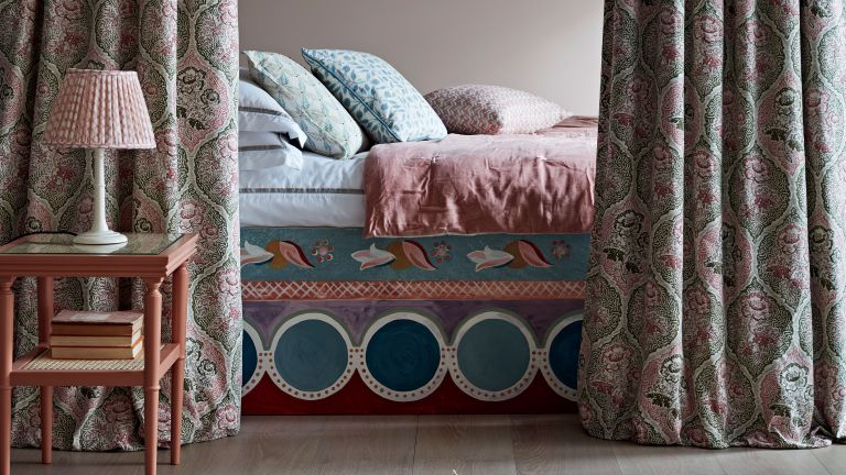 Cozy bedroom ideas in a rich, patterned scheme with alcove bed, drapes and bedside table.