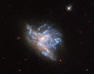 A Hubble Space Telescope image shows an object known as NGC 6052, which is made up of two relatively-nearby galaxies colliding just 230 million light years away.