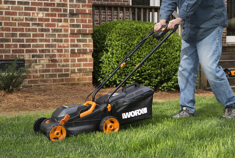 Man pushing the best small lawn mower a WORX 40V Power Share 4.0 Ah 14'' Lawn Mower