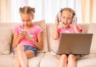 Two girls sitting on the couch using a smartphone and computer.