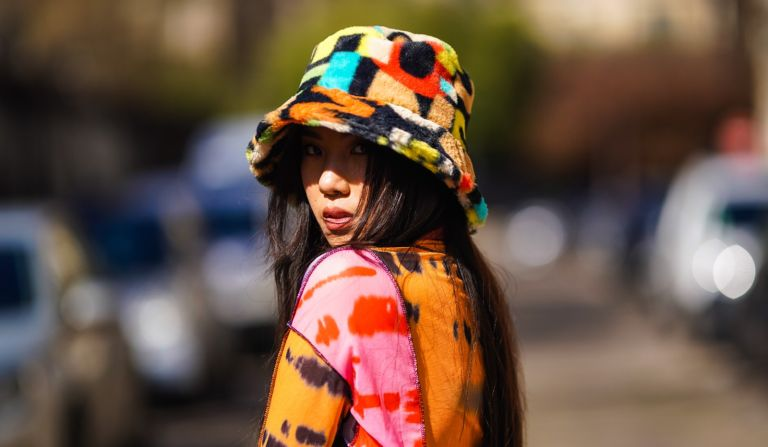 Alessandra Huynh @atiashuynh wears a fluffy colorful bob hat from Asos, a tie and dye multicolor top from Asos with printed patterns, a brown short vintage dress, on March 24, 2021 in Paris, France.
