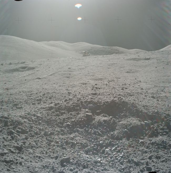 The crater containing sample 70019, with the Apollo 17 lunar module in the background.