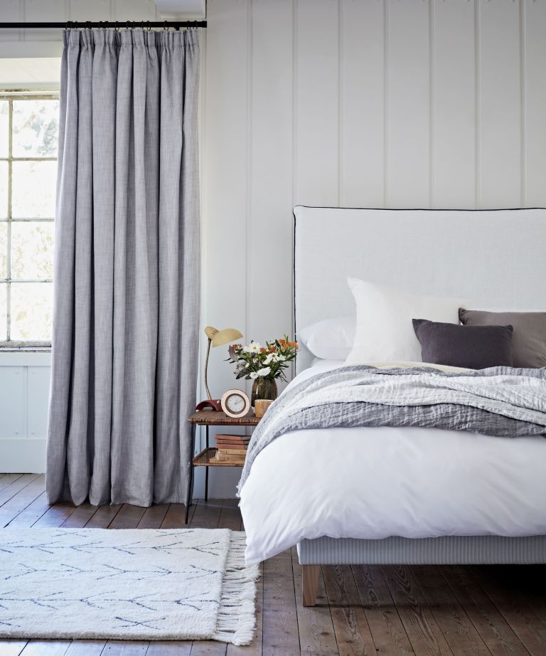 An example of how to design a bedroom showing a bedroom with denim-colored curtains with blackout lining and a white bed
