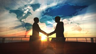 Two men in silhouette shake hands against a rising sun. Clouds form the shape of a world map.