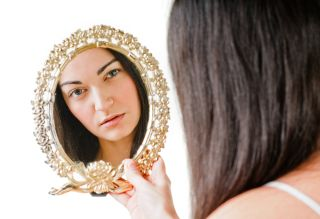 Woman looking in mirror, reflection