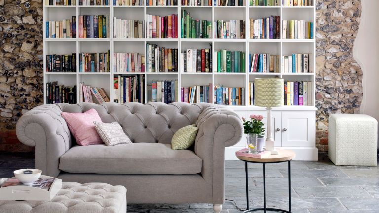 living space with grey sofa and bookshelves