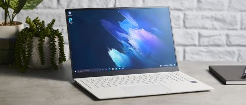 Samsung Galaxy Book Pro on wooden table with screen open and desktop shown