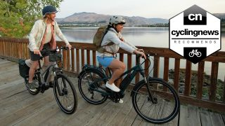 Two cyclists riding electric bikes in nature