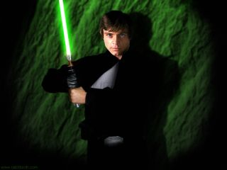 Luke Skywalker holds a light saber.