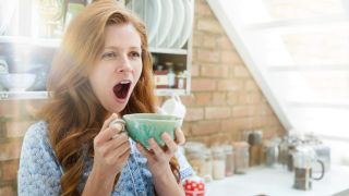 New study bursts the bubble on sleep deprivation and napping: A woman with red hair yawns while holding a blue cup in her kitchen