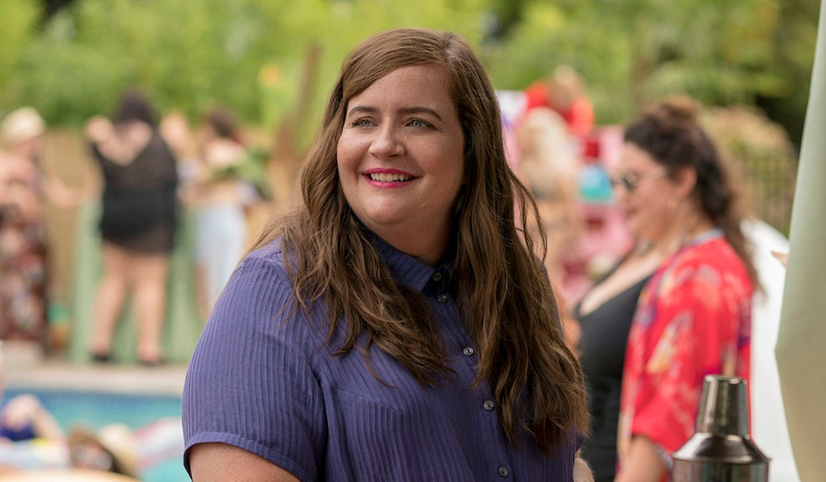Shrill Aidy Bryant smiling by the pool