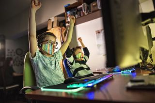 Two masked boys raise arms in victory at computer gaming station.
