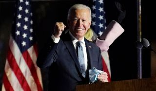 Joe Biden makes a fist pump while standing in front of two American flags.