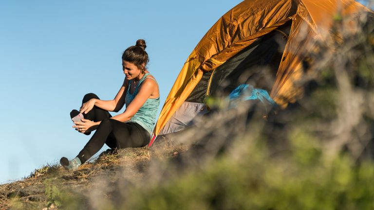 The best hiking socks: woman rubbing her feet outside her tent after a long walk