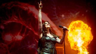 A picture of Nightwish's Floor Jansen doing the horn sign on stage at Download