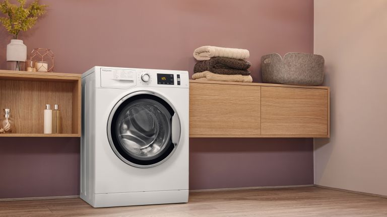 best washing machine: utility room with blush pink scheme and wooden sideboards and washing machine by AO