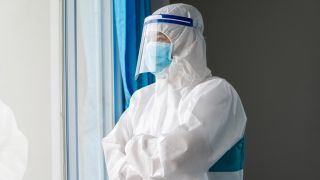 A doctor wearing a face mask and face shield to protect against COVID-19 in a hospital.