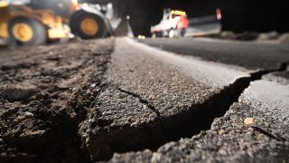 Highway workers repair a hole that opened in the road as a result of the July 5, 2019 earthquake in Ridgecrest, California, about 150 miles (241 kilometers) north of Los Angeles.