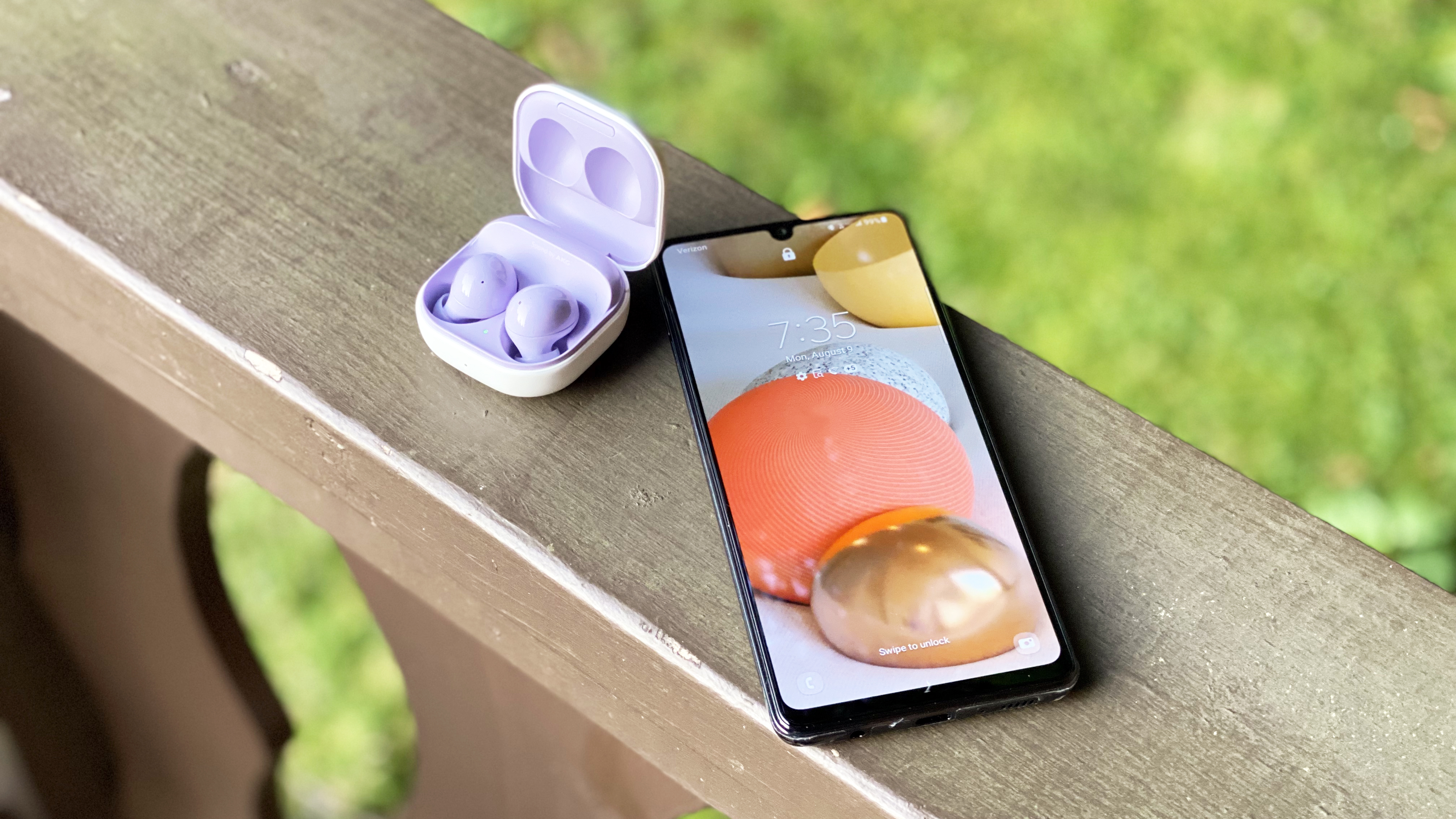 the samsung galaxy buds 2 next to a smartphone