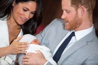 Prince Harry, Duke of Sussex, and Meghan, Duchess of Sussex, pose with their newborn son Prince Archie Harrison Mountbatten-Windsor in St George's Hall at Windsor Castle on May 8, 2019, in Windsor, England.