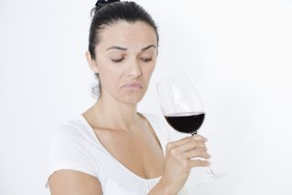 A woman stares at a glass of wine.