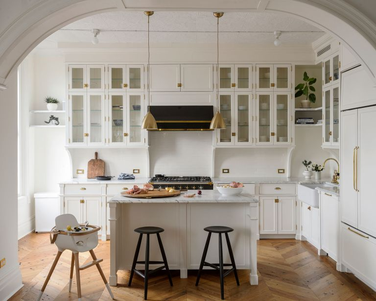 An example of how to organize a kitchen with white storage on the walls and kitchen island.