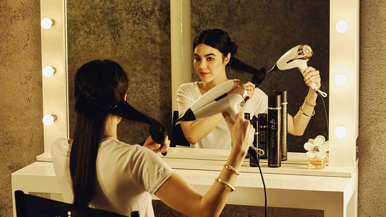 GHD Helios Hair Dryer - Professional Hairdryer (White) in use by woman in front of mirror