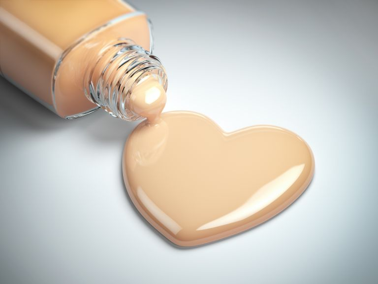 Liquid makeup foundation cream in form of the heart symbol and glass bottle