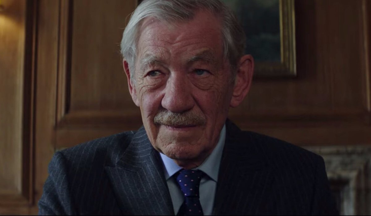 The Good Liar Ian McKellen smiling in his office during a transaction