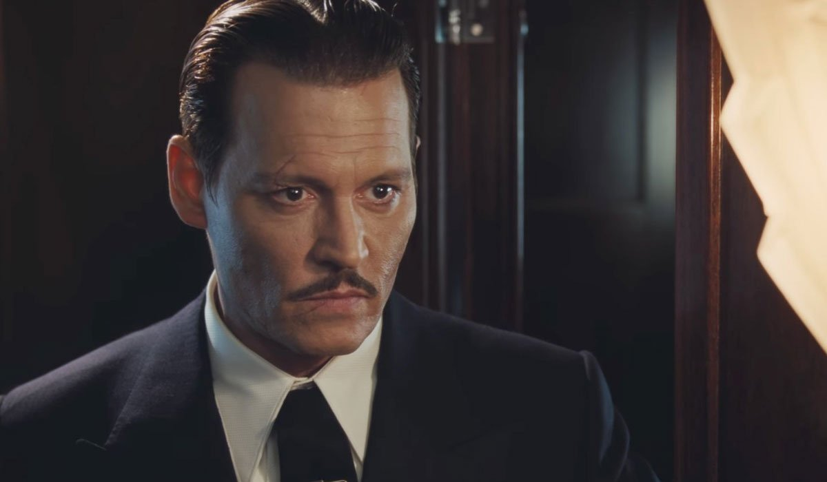 Johnny Depp In Murder On The Orient Express leans forward and looks intently at an unspecified objec