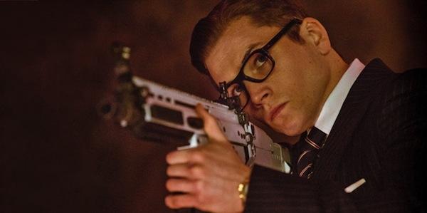 Kingsman The Secret Service Taron Egerton Eggsy aims a gun