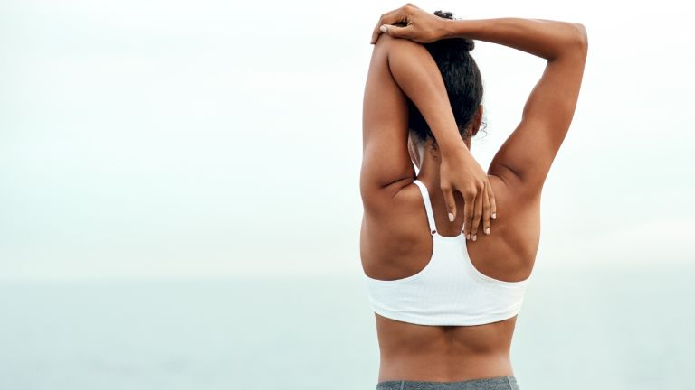 benefits of yoga on memory woman stretching looking out to sea