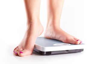 A woman stands on a bathroom scale.