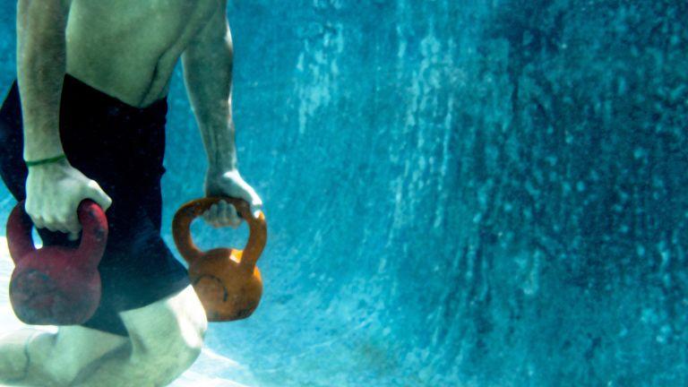 Man carrying kettlebells underwater
