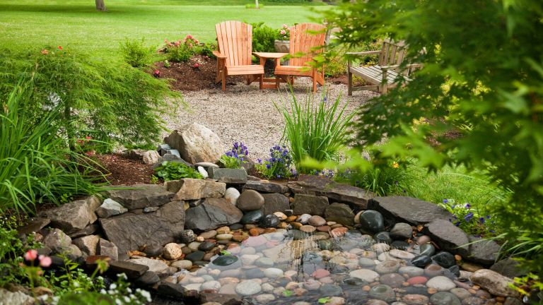 garden pond ideas: rocky pond with seating nearby