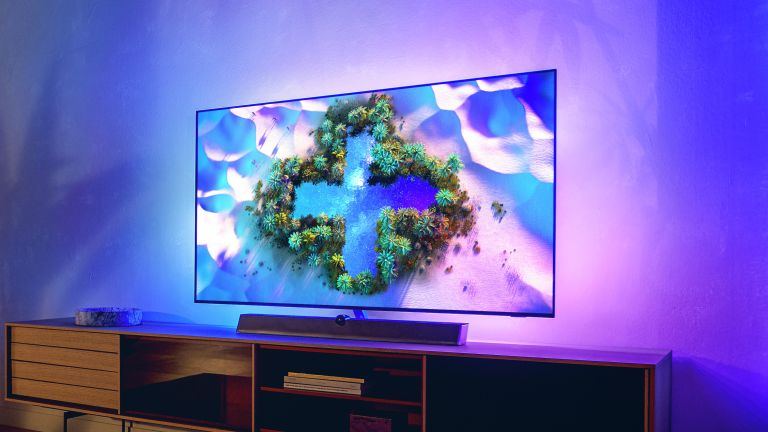 Philips OLED+936 sitting on wooden TV bench, with Ambilight light spreading onto the wall behind it