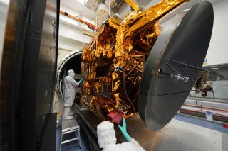 Engineers stand with the Hope Mars probe in a cleanroom.