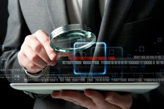 Man in suit examines laptop computer with magnifying glass, with binary code in foreground