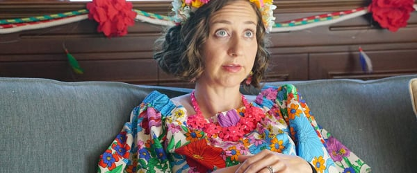 The Last Man On Earth Kristen Schaal dressed colorfully, sitting on a couch