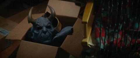 A scary horned blue devil mask sits in a cardboard box looking ominous