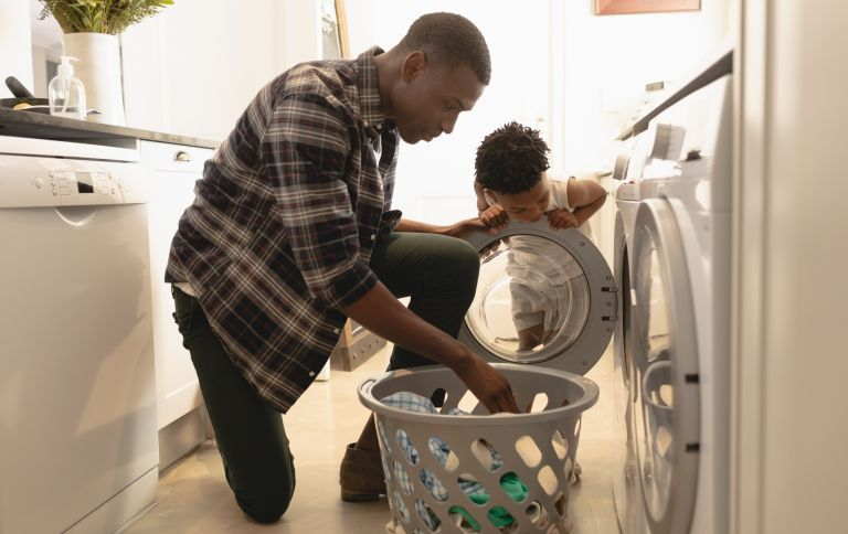 eco-friendly washing powder: Father and child putting clothes in a washing machine