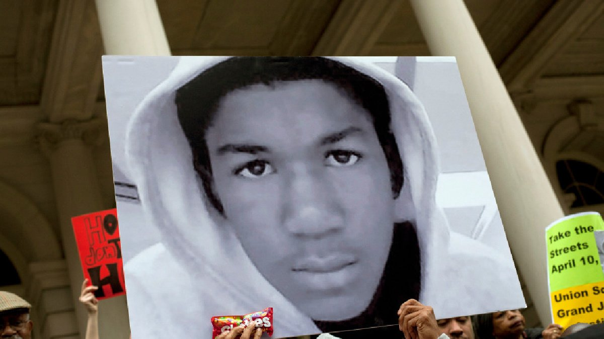 A protest showing a picture of Trayvon Martin recorded in the docuseries Rest in Power: The Trayvon Martin story.