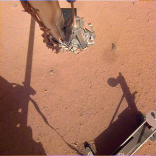 The robotic arm on NASA's Mars InSight lander moves in place over the Heat Flow and Physical Properties Package (HP3) and opens the fingers of its grapple in this image from June 1, 2019.